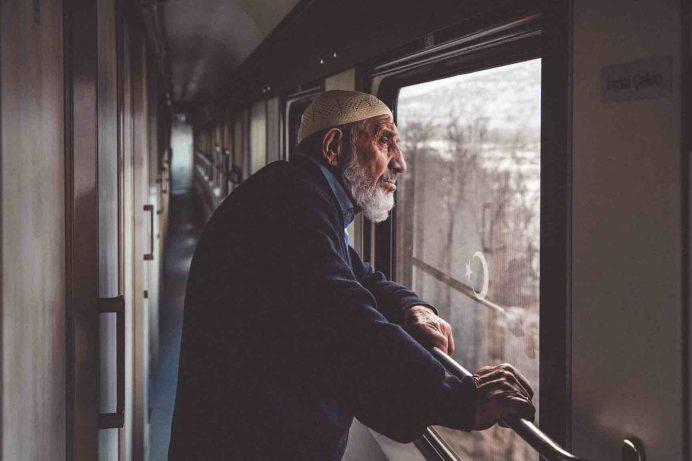 trenden dışarı bakan yaşlı insan